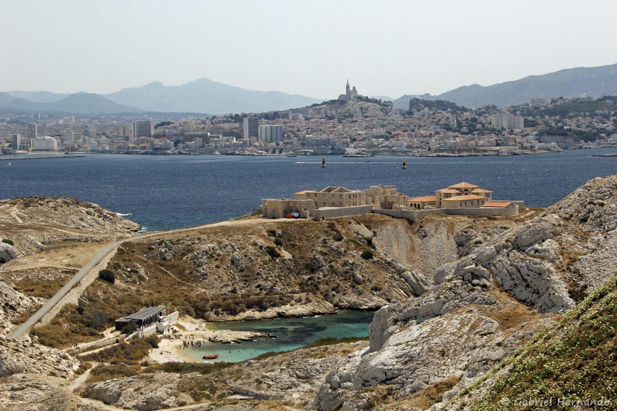 Plage de la calanque de Saint-Estève, et l'hôpital Caroline, sur L'île Ratonneau, avec Marseille et la Bonne Mère en arrière plan.
